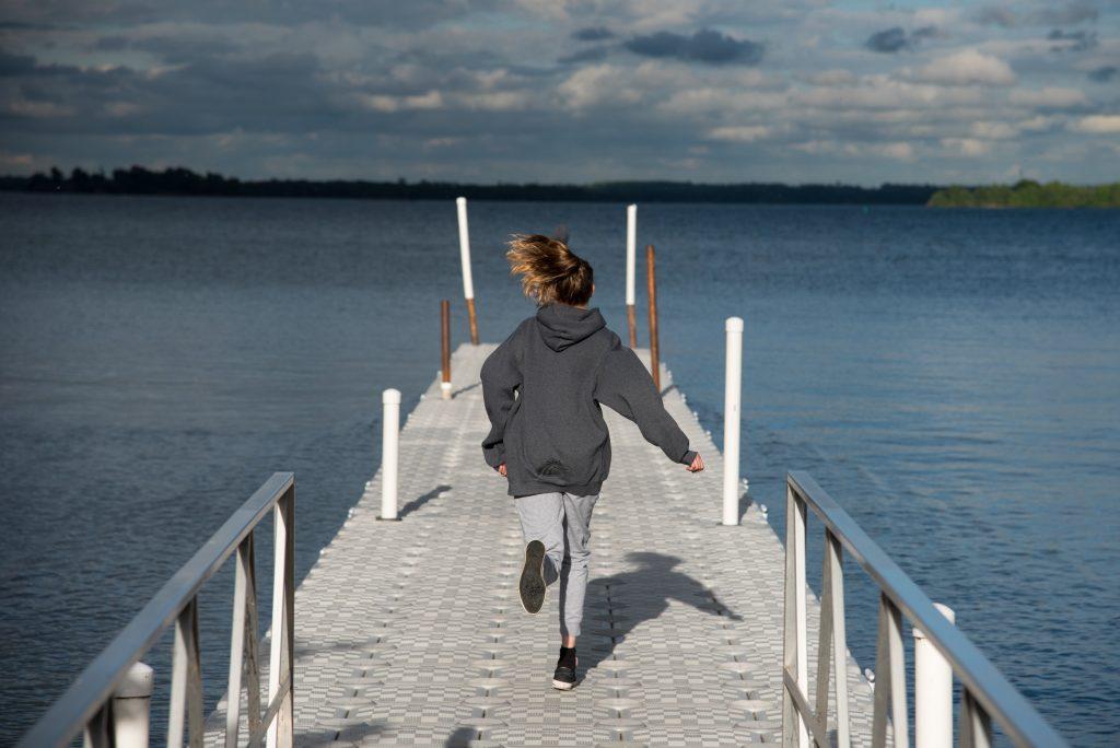 Girl running down dock